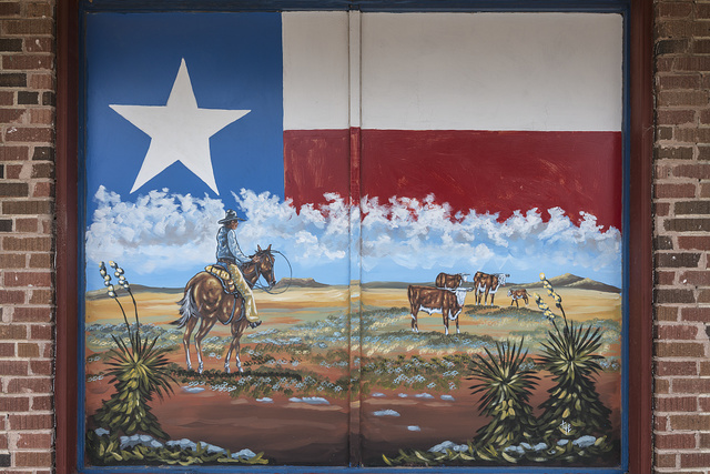Mural depicting the wide-open spaces of the Texas panhandle, with the Texas state flag as a backdrop, on a building in McLean, Texas, a town along old U.S. Route 66 in the panhandle