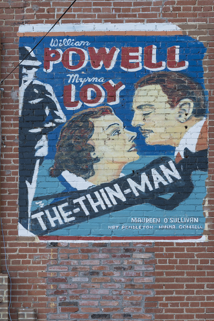Mural painted by artist Sunny DeLipsey of Athens, Texas, depicting an early movie poster, on the rear wall of the Books and Crannies bookstore located in the old Iris Theater building in Terrell, Texas, east of Dallas