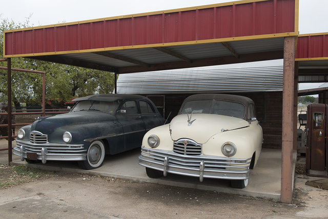 Old cars beneath an awning at a re-created Shell gasoline station at the Pottery Ranch pottery store in Marble Falls, Texas