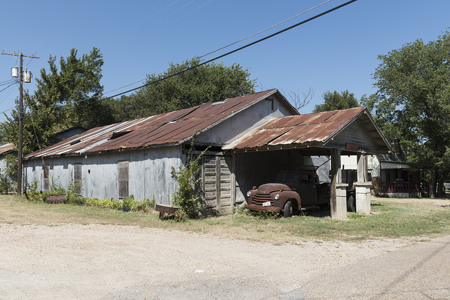 """Old truck under an older shed overhang in Italy, Texas. Gabriel J. Penn, postmaster in Waxahachie, 15 miles away, named the town in 1880 because, he said, its climate was much like that found in """"sunny Italy"""""""