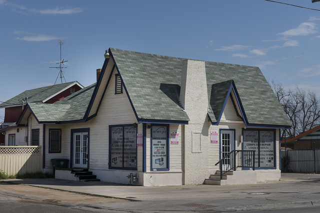 One of the old, architecturally iconic, English cottage-style Pure Oil gasoline stations with steep pitched roofs that once dotted the American landscape. This one, in Laredo, Texas, was added upon and, at the time of this photograph, served as a computer-repair shop