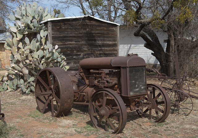 Prickly pear cacti and an old, rusty tractor near a shed at the Buffalo Gap Historic Village in the unincorporated Taylor County, Texas, town of the same name, near Abilene
