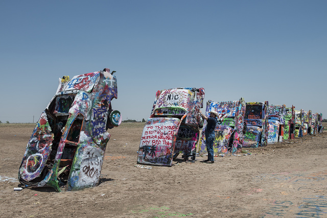"Robert Griffin is no spray-painting vandal. Like thousands of other visitors to the ""Cadillac Ranch"" along Old U.S. Route 66 outside Amarillo, Texas, he is encouraged to bring a along a spray can to add a touch or two to the unusual public art installation. Thus the overall look remains the same over time, but the details change daily"