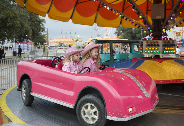 Samantha and Scarlett Santana have some fun in the ride area of a carnival outside the event locations Rodeo Austin, the city's annual stock show and rodeo. Austin, Texas