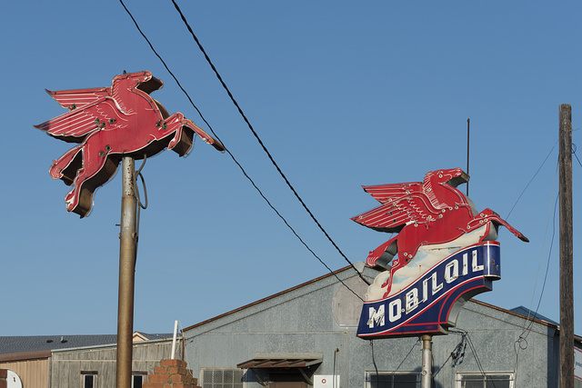 Side-by-side vintage Mobil pegasus (flying horse) gas station insigias along a road in East Texas