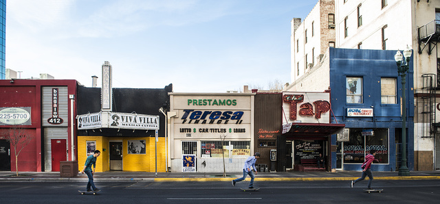 Skateboarders zip past a colorful row of small businesses in downtown El Paso, Texas