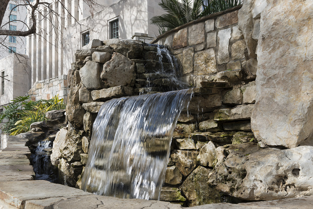 Stairway and man made waterfall at the River Walk, also known as the Passeo del Rio, a network of walkways along the banks of the San Antonio River, one story beneath the streets of Downtown San Antonio, Texas