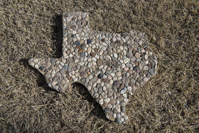Stone version of Texas in outline in the grass outside the Shackelford County Courthouse in Albany, Texas
