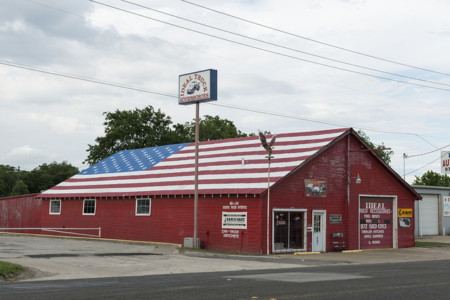 Truck-parts store with a colorful, patriotic-themed painted roof in Terrell, Texas, east of Dallas