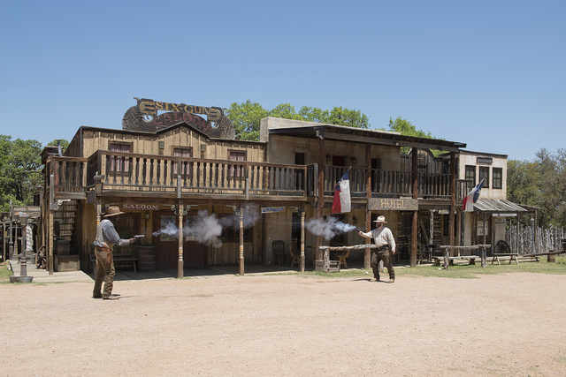 "Two ""gunslingers"" (historical intrepreters Thornton Young, left, and Wes Hughes) fire away in a showdown on the street at the Enchanted Springs Ranch, an Old West theme park, special-events venue, and frequent movie and television commercial set in Boerne, Texas, northwest of San Antonio"