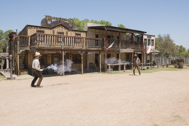 """Two """"gunslingers"""" (historical intrepreters Wes Hughes, left, and Thornton Young) fire away in a showdown on the street at the Enchanted Springs Ranch and Old West theme park, special-events venue, and frequent movie and television commercial set in Boerne, Texas, northwest of San Antonio"""