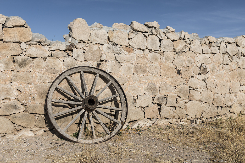 Wagon wheel and remnants of an old wall from the 20th-Century period when what is now Hueco Tanks State Historic Area near El Paso in El Paso County, Texas, was a privately owned ranch