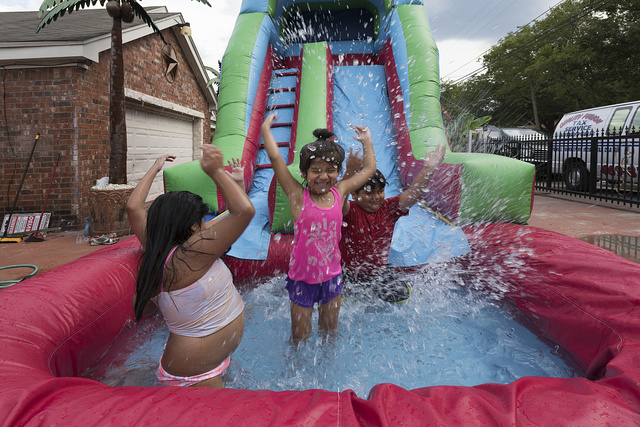 Yara, Dorsey, and Dominick Morales, left to right, play on an inflatable water slide outside their home in Dallas, Texas