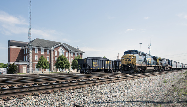 A diesel locomotive and freight cars, and a line of hoppers filled with coal, sit behind the CSX train station in Huntington, West Virginia