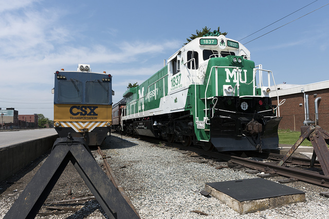 A diesel locomotive, painted in the colors and with the symbols of the local Marshall University, sits at the CSX station in Huntington, West Virginia. The railroad donated the locomotive and a passenger car to the university
