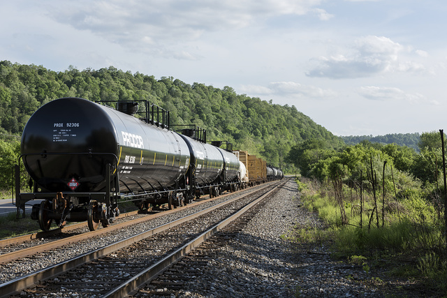 A long line of rail cars, mostly tank cars carrying propane, along West Virginia Highway 2 on the Ohio River in Tyler County