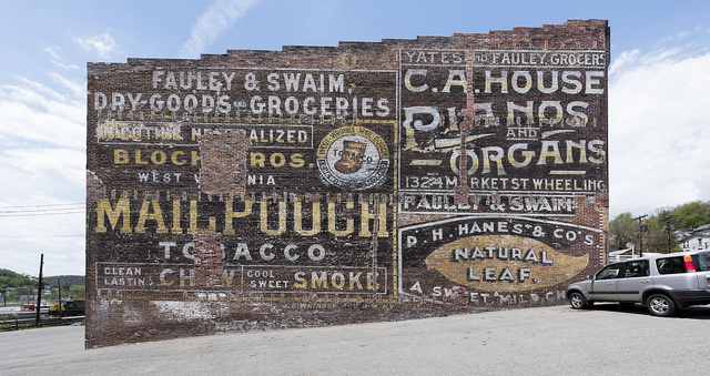 An old Mail Pouch Chewing Tobacco sign, and other advertisements, on a wall in downtown Grafton, West Virginia