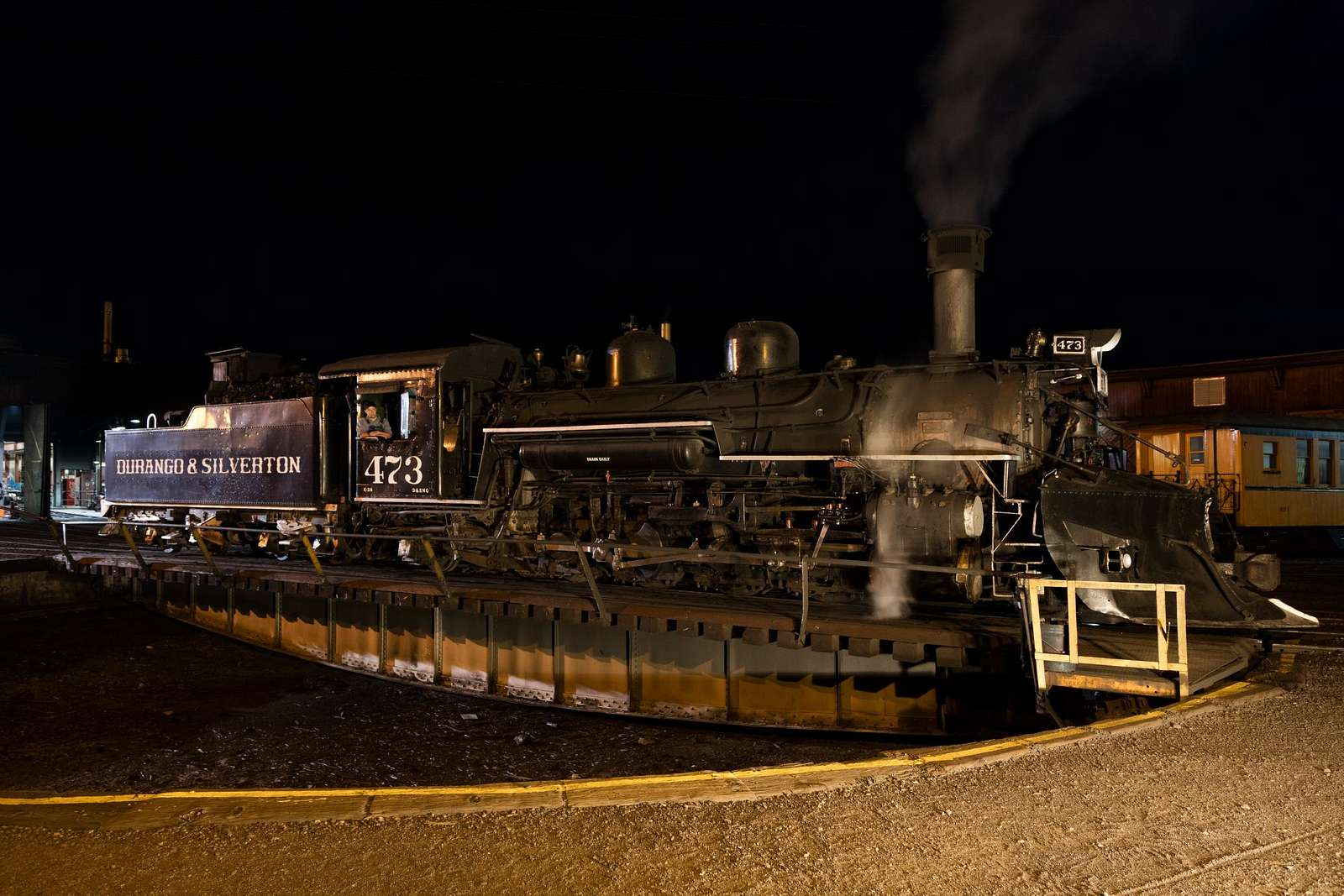 Steam locomotive and coal tender in on a roundhouse turntable in the trainyard of the Durango & Silverton Narrow Gauge Scenic Railroad in Durango, Colorado