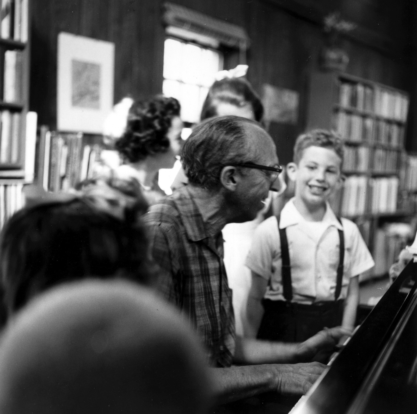 Aaron Copland at piano, family reunion, with admiring grandnephew, ca. 1958