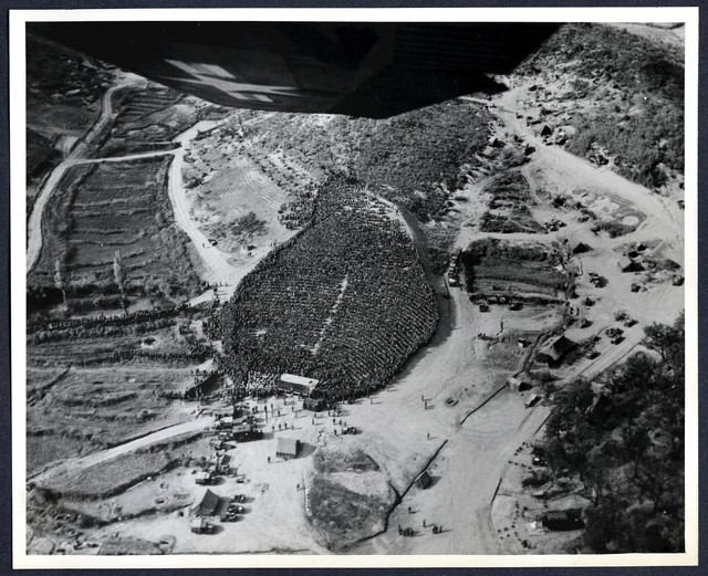 Aerial view of troops in the 1st U.S. Va. Div. Numbering 15,000, who gathered on Hillside at Div. HQS, Korea to enjoy the USO show starring comedian Danny Kaye, and singer Monica Lewis, MGM Motion Picture Actress