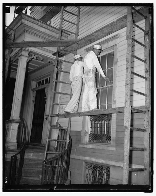 A.F. of L. paints home of John L. Lewis. Washington D.C., July 14. John L. Lewis Head of the C.I.O. is having his newly purchased home in Alexandria, VA reconditioned by the members of the American Federation of Labor his rival in the labor disputes. Photo shows two of the A.F. of L. painters at work on the house, 7/14/37