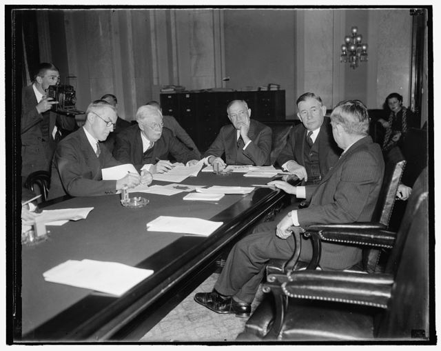 Agriculture secretary gives views on housing to senate committee. Washington, D.C., Dec. 3. Members of the Senate Banking and Currency Committee hear Secretary of Agriculture detail the steps he is taking to bring farmers within the scope of the New Housing Program proposed by President Roosevelt. In the photograph, left to right: official Senate reporter; Senator John G. Townsend; Senator Robert F. Wagner; Majority Leader Alvin Barkley; and Secretary Wallace. 12/3/37