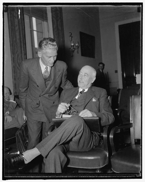 """Appear before house rivers and harbors committee. Washington, D.C., Nov. 23. Stuart Chase, (left) New York economist, and L.C. Sabine, of Cleveland, Vice-President of the Lake Carriers Association, were the first witnesses called today as the House Rivers and Harbors Committee began hearings on a bill to create seven Regional Planning Authorities. Chase told the committee """"that free competition no longer is operating over a broad part of the economic front."""" He predicted further dislocation of man and his natural resources unless there is planned economics and conservation. 11/23/37"""
