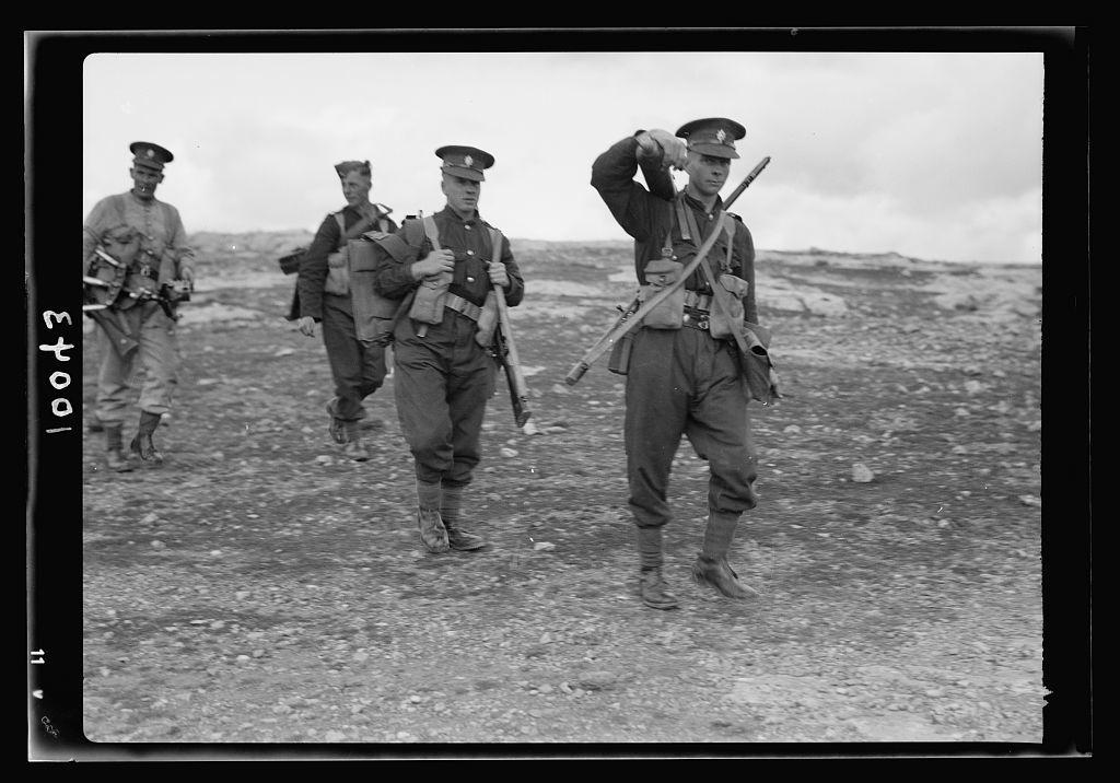 Arab demonstration at Yatta. British troops on the hill-side carrying machine guns & full equipment