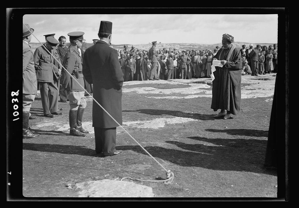 Arab demonstration at Yatta. Peasant reading propagand[a] sheet prepared by Fakhri Nashashibi who is seen in the picture with his back to the camera
