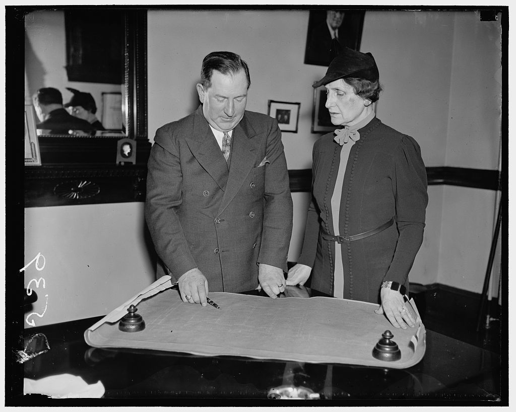 As Uncle Sam prepares to move his gold from the mint to his new safe in Fort Knox, Ky. Philadelphia, Jan 11/37. Edwin H. Dressel, Superintendent of the Philadelphia Mint, and Mrs. Nellie Taylor Ross, Director of the Bureau of Mints confer preparatory to supervising the tranferring the gold in the Philadelphia Mint to Fort Knox, Ky., where all the gold reserve of the United States will be accumulated