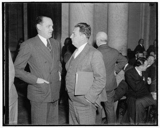 At Monopoly hearing. Washington, D.C., Dec. 1. Dr. Willard Thorp, left, Dun and Bradstreet Economist not with the Commerce Department. Leon Henderson, Secretary of the Joint Monopoly Committee, chat informally as both attended the opening hearing today. They will testify before the Committee tomorrow