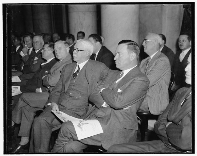 Attentive listeners. Washington, D.C., Nov. 1. Nathan L. Miller, General Counsel for U.S. Steel Corp., and Benjamin F. Fairless, President of the U.S. Steel Corp., listen attentively as the first witness testified when the National Monopoly Committee began its study today of the $4,000,000,000 steel industry