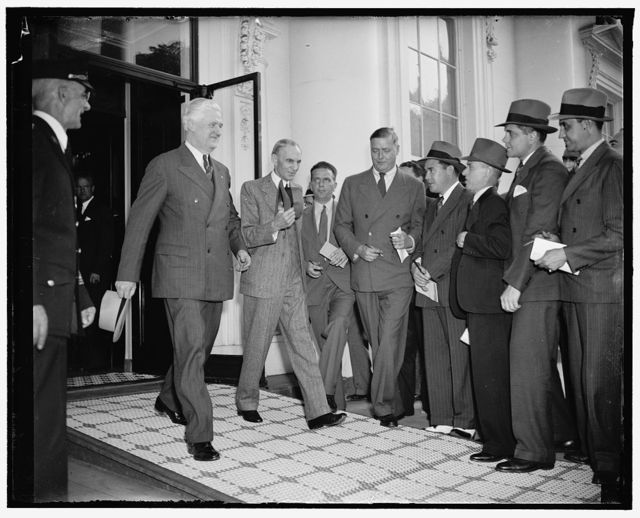 Auto magnate leaves White House after conference with President Roosevelt. Washington, D.C., April 27. Forced to run a gantlet of newspaper reporters, Henry Ford is pictured leaving the White House today with Maj. Henry M. Cunningham, Manager of the Alexandria, VA.O branch of the Ford Motor Co., after a luncheon and conference with Presdient Roosevelt. Both the White House and Ford refused to make a statement following the discussion which lasted a couple of hours, 4/27/38
