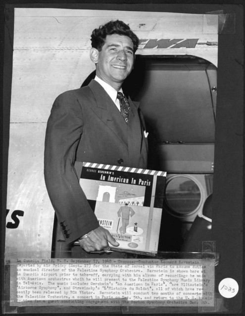 Bernstein departing for Israel to assume duties as musical director of the Israel Philharmonic Orchestra (IPO). He is carrying recordings he made with American orchestras to present to the IPO Music Library. The recordings include Gershwin's An American in Paris. Marc Blitzstein's Airborne Symphony and Igor Stravinsky's L'histoire du Soldat. September 17, 1948. Photograph source: Enell, Inc. (Music Division)