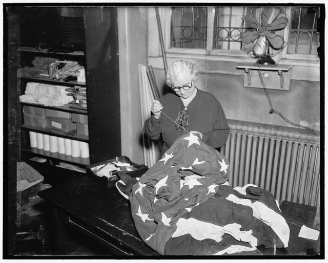 """""""Betsy Ross of the Capitol."""" Washington, D.C. Mrs. Georgeieanna Higgins. Official title is Seamstress to the United States Senate, but for years has been called the """"Betsy Ross of the Capitol."""" She is responsible for keeping the flag that flies over the Senate wing of the Capitol in proper flapping order. This is no mean job since the flag flies night and day when the Senate is in session, which means a terrific beating from the elements, an average of 12 Flags is used each session"""