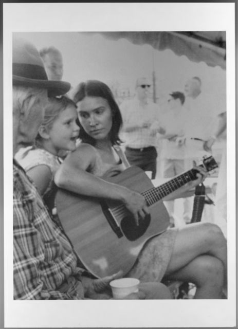 Bobbie Thompson of the Hollow Rock String Band playing on guitar and talking with her daughter, Jessica, with Henry Reed looking on. Narrows (Virginia) Fiddlers Contest, summer 1967.