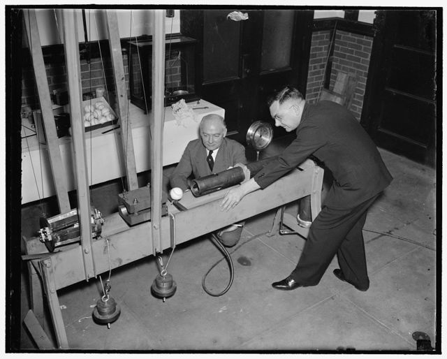 Bureau of Standards designs mechanical batter to determine liveliness of baseballs. Washington, D.C., Feb. 21. Using a newly designed apparatus, the U.S. Bureau of Standards today began experiments to determine the relative home-run qualities of American, National and International baseballs. In conducting the tests a scientist pulls the trigger of an air gun loaded with a wooden projectile representing the slugger's bat. The projectile strikes a baseball causing it to fly toward a ballistic pendulum. After each of such hits the scientist takes a reading on the pendulum. It tells him how hard the ball hit the pendulum, or whether it was a homerun, a double, [...]st a pop fly. Dr. H.L. Dryden, Chief [...]e Division of Mechanics and Sound, Designed the machine and is supervising the tests. He is [...] right while on the left is Edward B. Eynon, Secretary of the Washington Baseball Club, 2/21/38