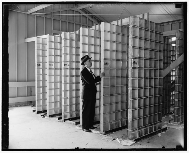 Bureau of Standards making extensive tests of glass building blocks. Washington, D.C., June 20. Hollow glass building blocks are being used more and more extensively for structural purposes when both greater light distribution and air conditioning are required. Extensive tests to determine the strength of glass block walls and their resistance to wind pressure and moisture penetration. A.N. Finn, Chief of the glass section, is inspecting some 8 x 4 feet panels before they are tested, 6/20/38