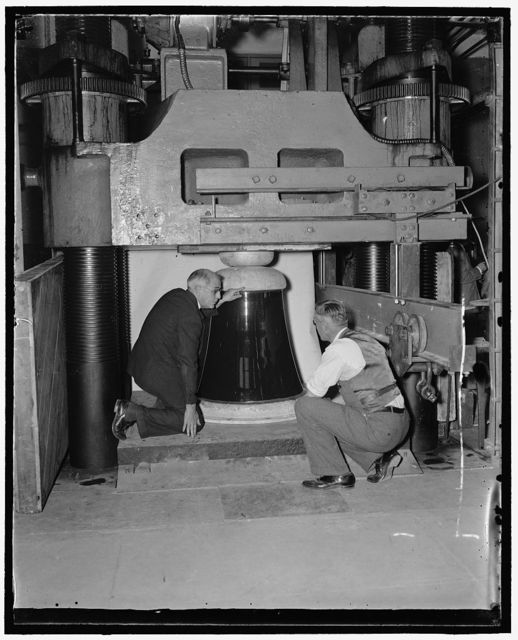 Bureau of Standards puts ruge insulator through pressure tests. Washington, D.C., Nov. 30. H.L. Whitemore, (left), chief of the Engineering Mechanics section, National Bureau of Standards, and Dr. A.H. Stand, make a final check of the huge 1600[?] pound porcelain insulator before subjecting it to 2,180,000 pounds pressure in the Bureau's hydraulic jack. The insulator, one of the few of its size in existence, will serve as a base for a 640 foot mast at Radio Station WGY, Schenectady, New York. One of the insulators successfully stood the pressure to 800,000 pounds while the second broke when the pressure was boosted to 2,180,000 pounds. The hydraulic jack is capable of exerting 10,000,000 pounds pressure