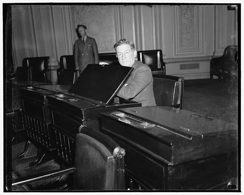 California Senator-elect gets 'feel' of desk in Senate chamber. Washington, D.C., Dec. 12. Senator-elect Sheridan Downey of California gets the 'feel' of the desk in the Senate chamber assigned to him today and which he will occupy when congress convenes on January 3. Downey succeeds William Gibbs McAdoo, whom he defeated in the November election, 12/12/38