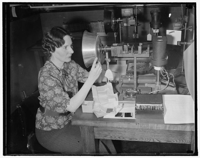 Checks railroad signal glasses for government. Washington, D.C., Sept. 29. Red should be read and orange should be orange and never should the colors in railroad signal glasses be so near alike as to confuse a trainman. The Government, through Mrs. Geraldine W. Haupt, Color Expert of the National Bureau of Standards, tests all railroad signal glasses to determine if the color value is true and also to see that they conform to certain specifications. 9/29/37