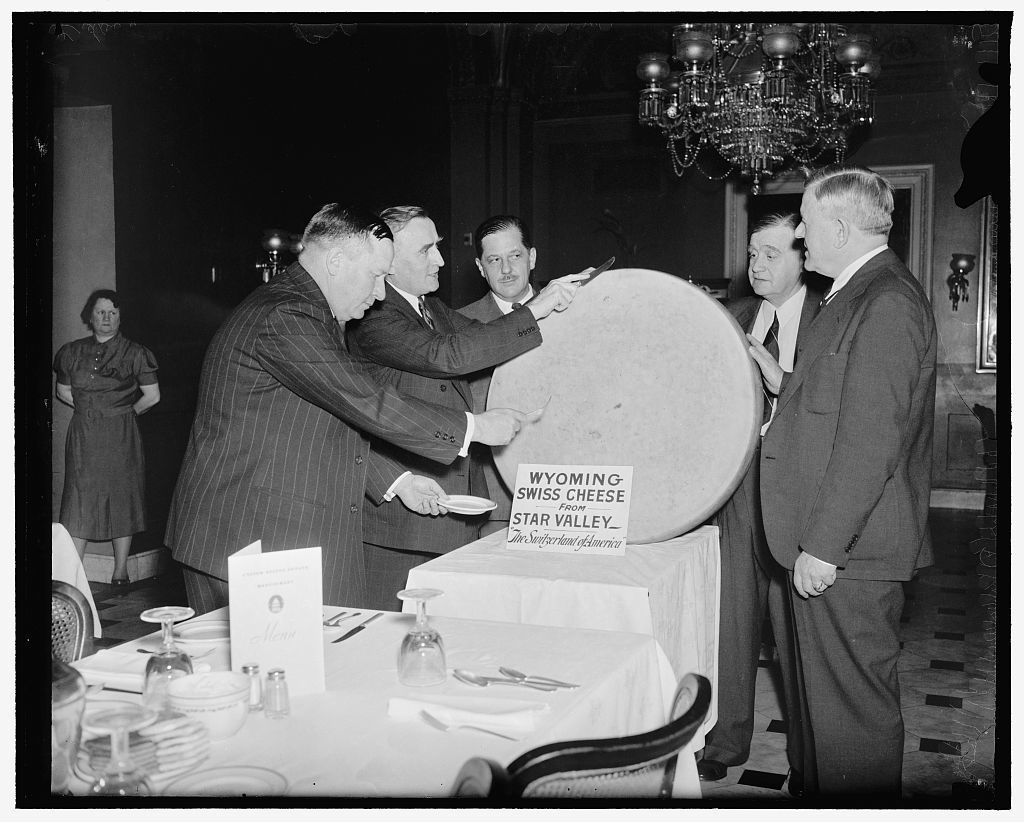Cheese party for statesmen. Washington, D.C., June 4. The famous swiss cheese from The Star Valley of Wyoming was the piece of resistance at the Capitol today for the members of Congress and other high government officials hailing from the state. The cheese weighed 250 pounds. Left to right: Rep. Paul R. Greener; Sen. Joseph D. O'Mahoney; Thurman Arnold, Assistant Attorney General; Fred W. Johnson, Commisioner, General Land office; and Senator H.H. Schwartz, 6/4/38