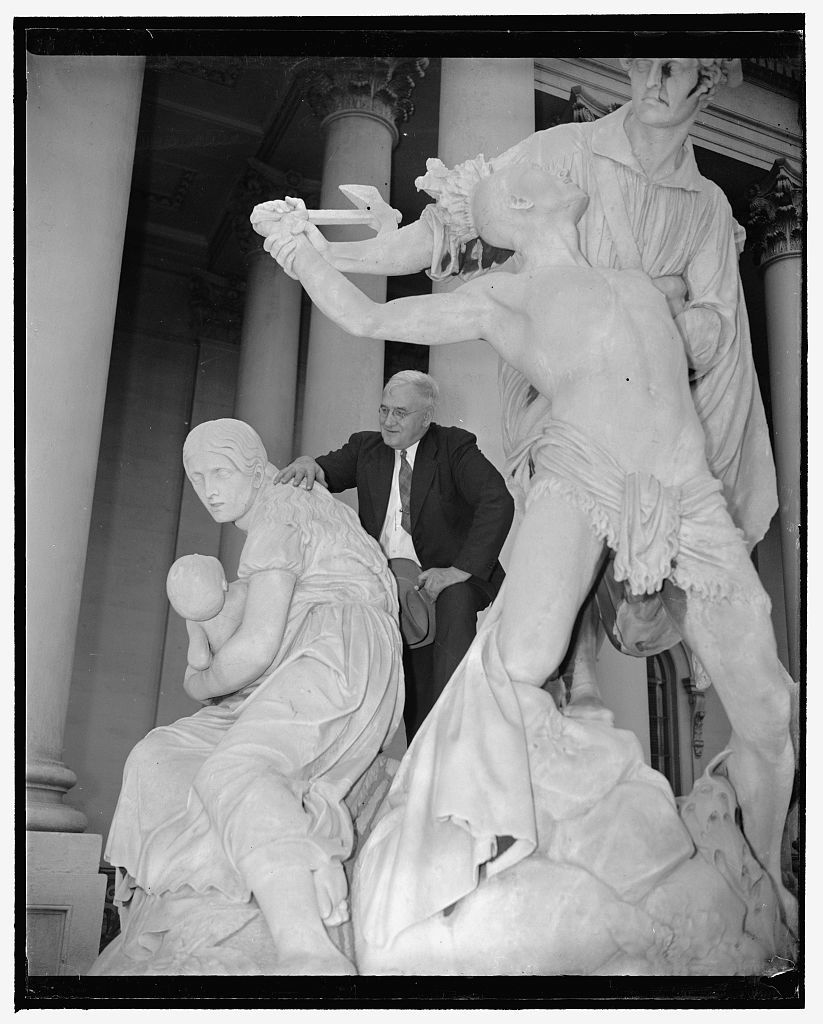 Congress urged to remove tomahawk-swinging Indian statue from steps of Capitol. Washington, D.C., April 27. If Rep. Usher Burdick, Republican of North Dakota has his way, the 87 year old statue standing on the steps of the Capitol which depicts a frontiersman rescuing a white woman from a possible redskin tomahawking will 'be ground into the dust and scattered to the four winds.' Introducing a resolution in the House to that effect, the legislator said, ' the American Indian was no worse than some of our own ancestors, and there is no more reason to memorialize his misdeeds than there would be to set up a monument to the witch burners of Salem'