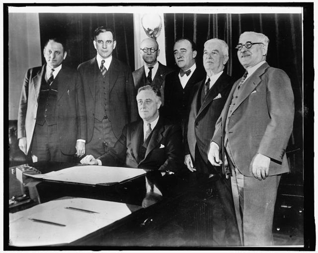 Congressional beer crusaders witness signing of beer bill. Members of Congress today witnessed the actual signing of their hard fought battle for legalized beer. Surrounding President Roosevelt at his desk in the Cabinet Room are, left to right: Representatives Claude V. Parsons of Illinois; John W. McCormack of Mass.; Clerk of Committee, H.V. Hesselman who brought the Bill to the White House; and Representatives John J. O'Connor of New York; Thos. H. Cullen and Adolph J. Sabath of Illinois, 3/22/33