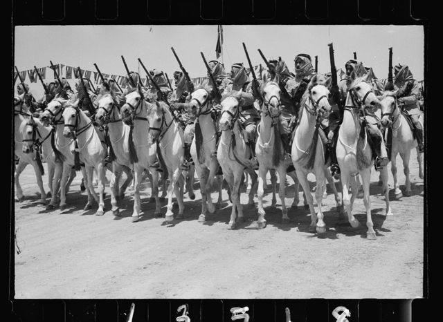 Coronation of King Abdullah in Amman on May 25, '46. The Elite Camel Corps of the Arab Legion, passing saluting ba[se]