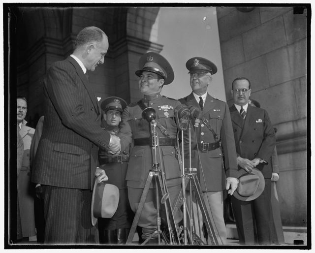 Cuba's Dictator greeted upon arrival. Washington, D.C., Nov. 10. Sumner Wells, The Undersecretary of State, shown shaking hands with Col. Fulgencio Batista as Gen. Malin Craig, the Chief of Staff of the U.S. Army looks on, 11/10/38