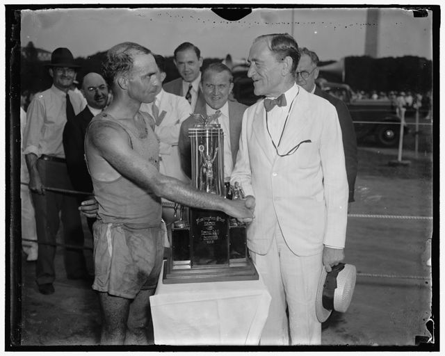 Cup to winner of marathon. Washington, D.C. June 12. Winner of the sixth annual Evening Star Marathon for the National A.A.U. Championship today, Mel Porter of the Millrose A.A. of New York is presented with a bronze trophy by Dr. Leo S. Rowe, Director of the Pan-American Union. A field of the fastest marathon runners in the western hemisphere participated in the race which started at Mt. Vernon, VA. and finished at the zero milestone in Potomac Park. Porters time for the distance was 2 hours and 43 minutes.