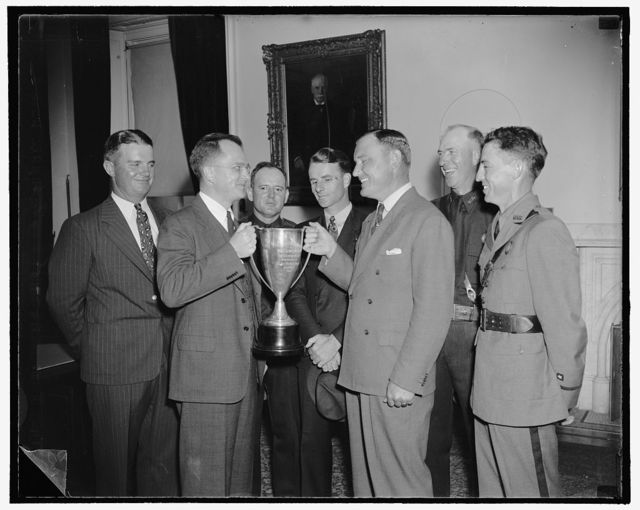 Custums rifle team receives secretary of treasury cup for marksmanship. Washington, D.C., Aug. 5. Acting Secretary of the Treasury, Roswell Magill today presented to the Bureau of Customs revolver team the silver cup offered by Secretary Morgenthau for proficiency in small-arms marksmanship by Treasury Agents engaged in law enforcement and protective duties. In the photograph, left to right: A.W. Quick, Norfolk, VA. Bureau of Customs; Acting Secretary Magill; M.R. Rogers, Seattle Bureau of Customs; W.J. Osmer, New York Bureau of Customs; P.M. Chapman, Takoma, Wash. Bureau of Customs; and E.L. Ballinger, El Paso, Tex. Bureau of Customs, 8/5/38