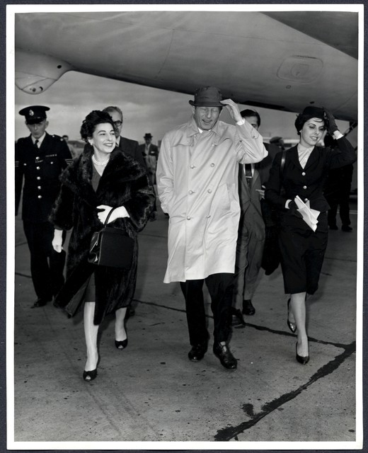 """Danny Kaye and his wife, Sylvia Fine, are a little wind-swept on arrival at London Airport [for the European premiere of """"The Five Pennies""""]"""