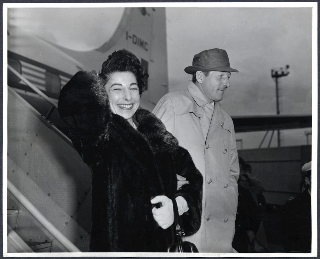 """Danny Kaye and his wife, Sylvia Fine, arrive at London Airport from the Continent [for the European premiere of """"The Five Pennies""""]"""